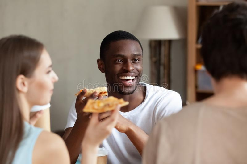Smiling African American man eating pizza, chatting with friends stock photography