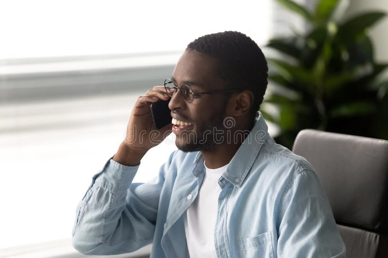 Smiling african American man having pleasant smartphone call royalty free stock photo