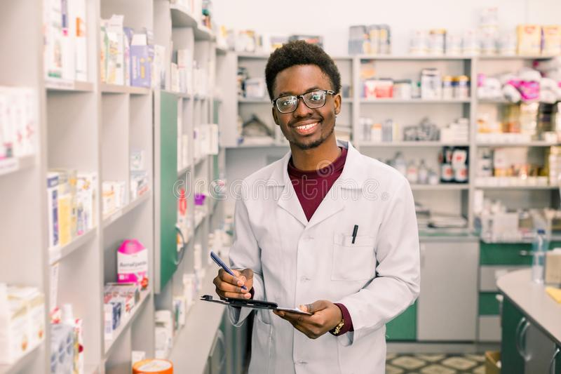 Smiling African American man pharmacist or Chemist Writing On Clipboard While standing in interior of pharmacy royalty free stock photo