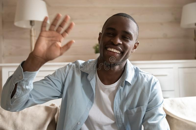 Smiling african American man wave having video call royalty free stock images
