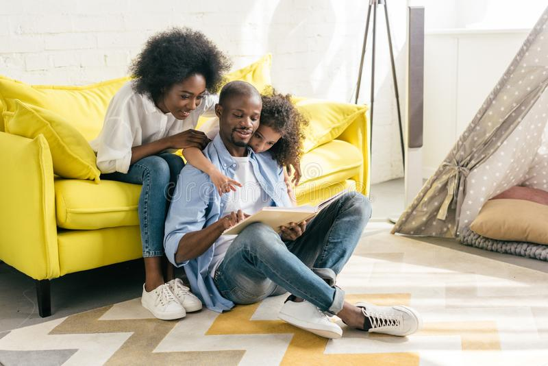 smiling african american parents and little daughter reading book together stock image