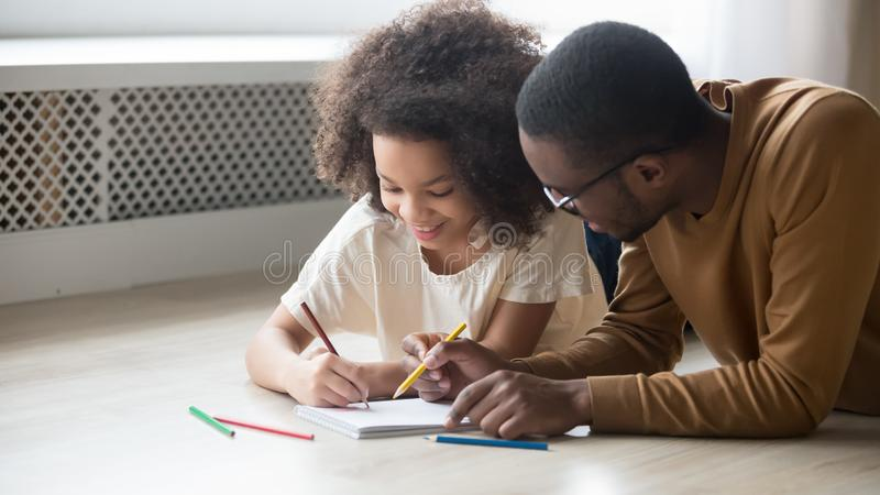 Smiling African American preschool daughter and father drawing pencils. Smiling happy African American preschool daughter and father in glasses drawing colorful stock photo