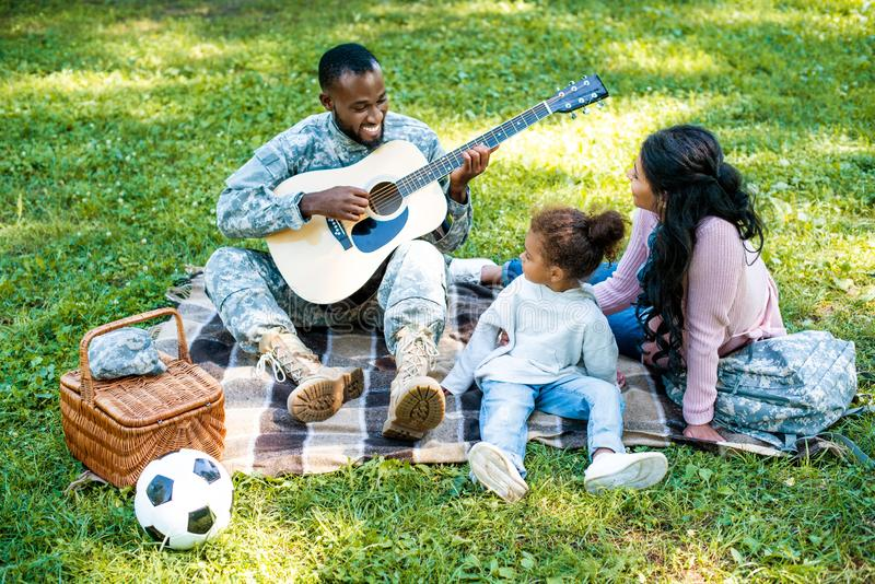 smiling african american soldier in military uniform playing guitar for family stock photos