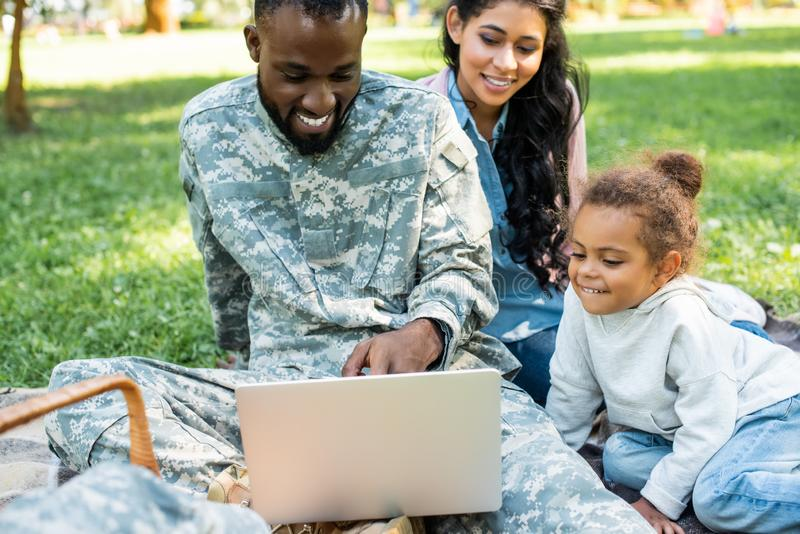 smiling african american soldier in military uniform using laptop with family royalty free stock images