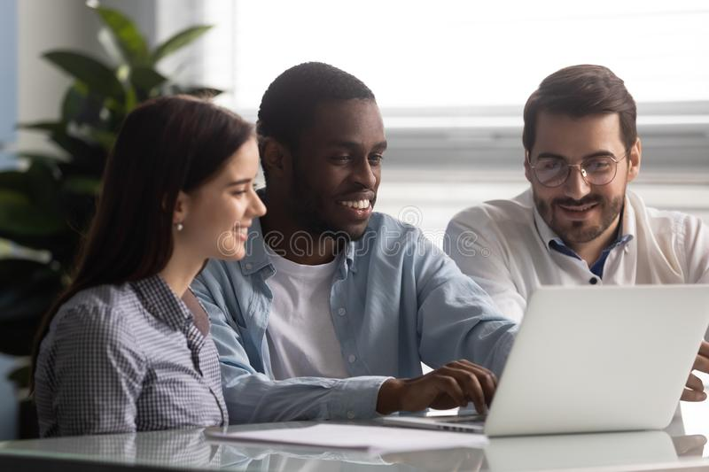 Smiling african american team leader working on computer with colleagues. stock images
