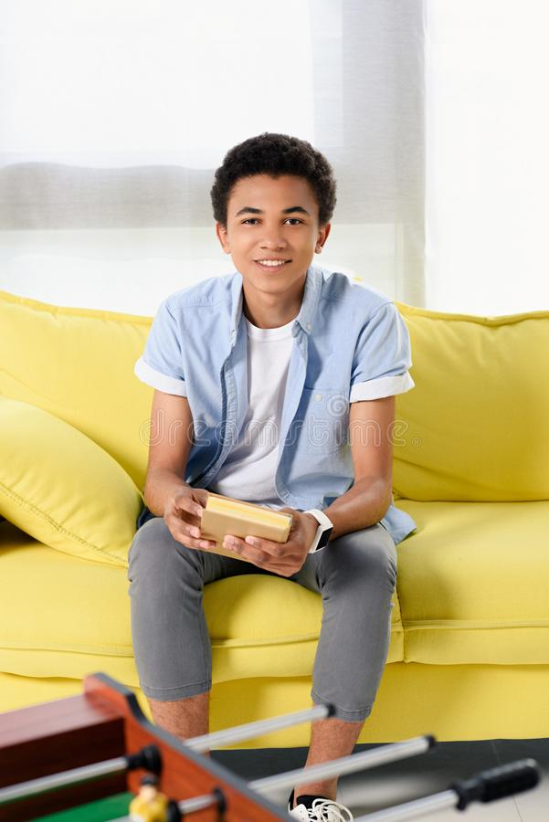 Smiling african american teenager sitting with book on yellow sofa. At home stock photos