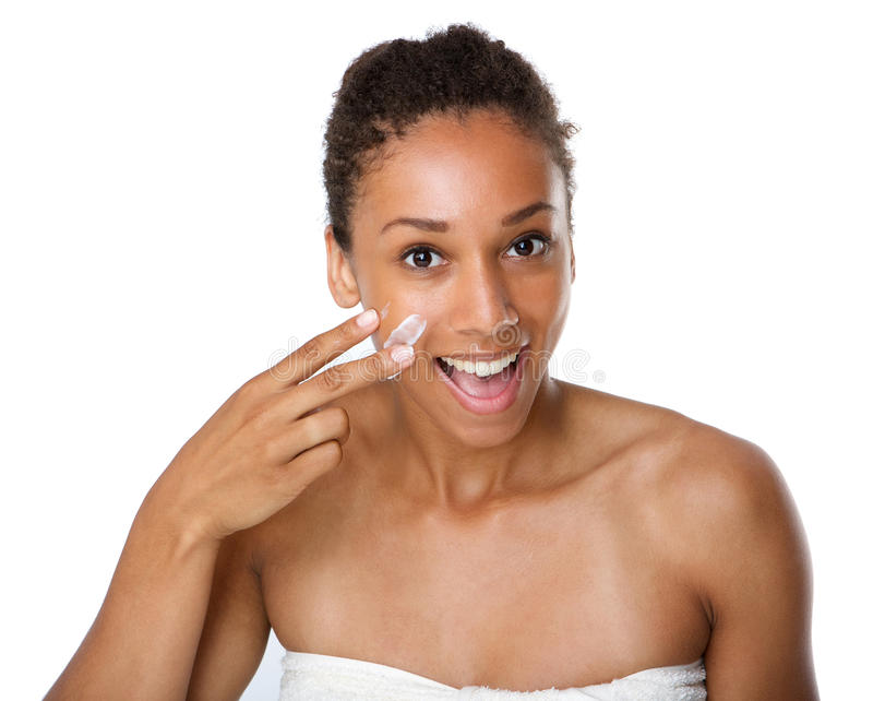 Smiling african american woman applying lotion on skin stock photography