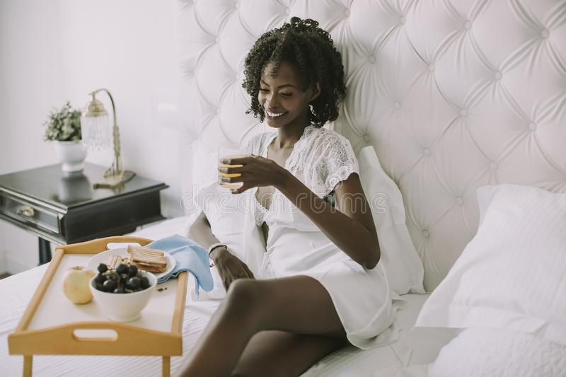 Smiling african american woman having a relaxing breakfast in be royalty free stock photos