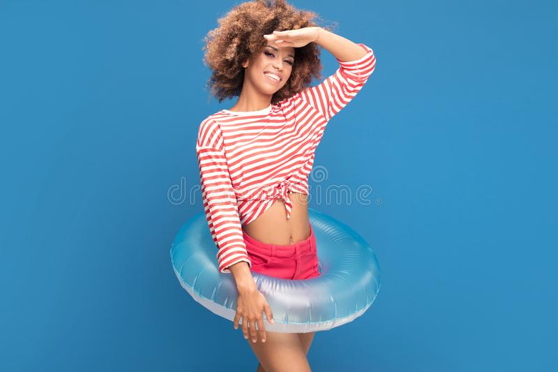 Smiling afro woman in sailor style shirt. Smiling african american woman posing on blue background, wearing shirt in white and red stripes, holding inflatable stock photo