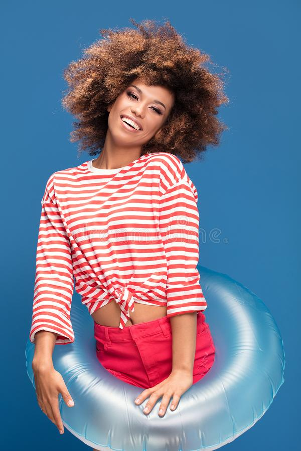 Smiling afro woman in sailor style shirt. Smiling african american woman posing on blue background, wearing shirt in white and red stripes, holding inflatable royalty free stock photography
