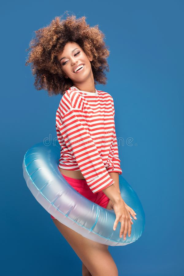 Smiling afro woman in sailor style shirt. Smiling african american woman posing on blue background, wearing shirt in white and red stripes, holding inflatable stock image
