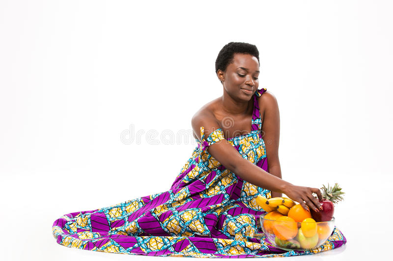 Smiling african american woman sitting with glass bowl of fruits royalty free stock photos