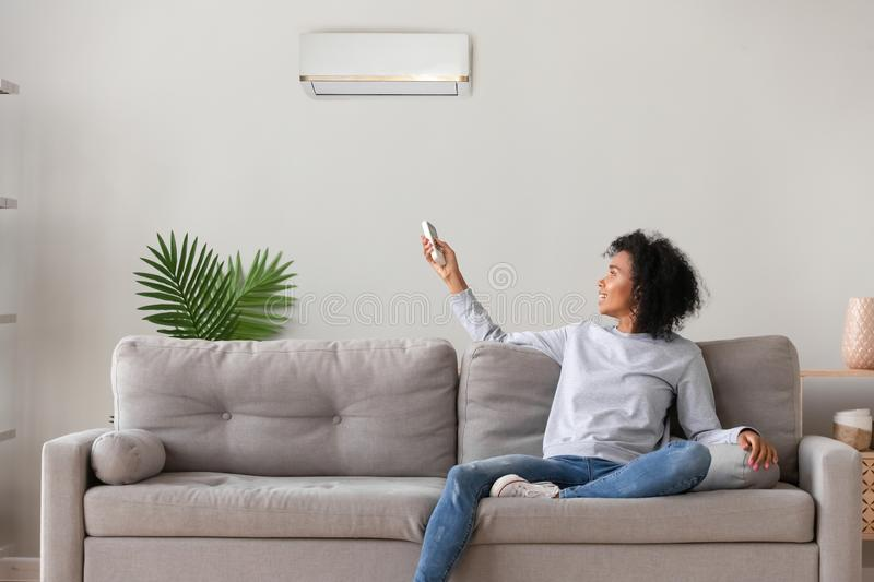 Smiling African American woman using air conditioner remote controller. Smiling young African American woman using air conditioner, cooler system remote stock photos