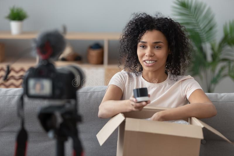 Smiling African American woman vlogger demonstrating cosmetics, unboxing royalty free stock images