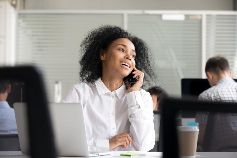 Smiling African American woman talking on phone at workplace stock photography