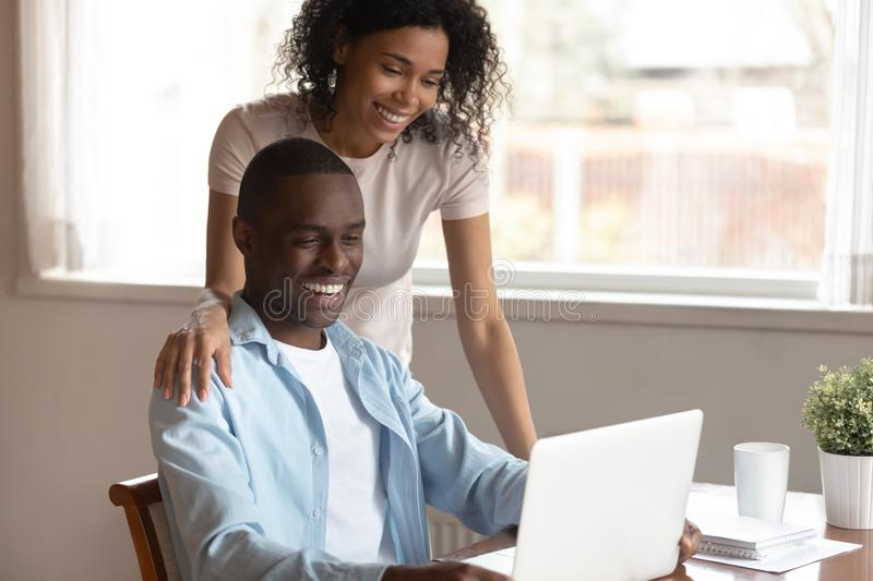 Happy biracial couple look at laptop screen using internet. Smiling african American young couple look at laptop screen use free wireless internet at home, happy stock photo
