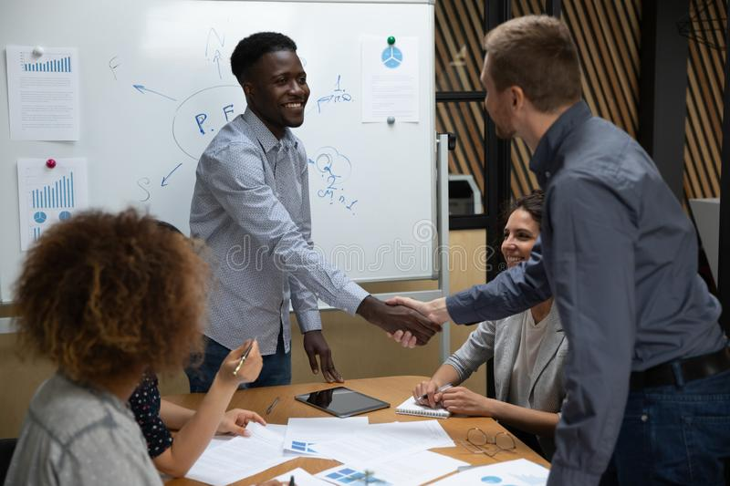 Smiling african american young leader shaking hands with caucasian colleague. stock images
