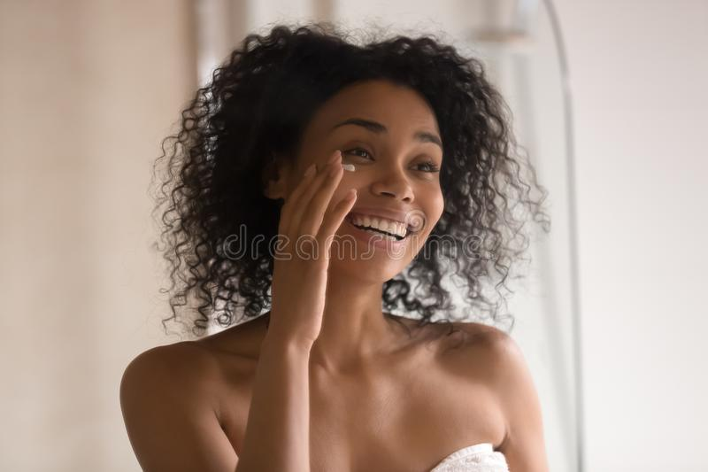 Smiling biracial woman apply under eye cream looking in mirror. Smiling african American young woman wrapped in towel after shower look in mirror apply under eye royalty free stock image