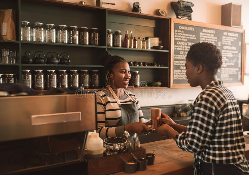 Smiling African barista handing a customer her drink order royalty free stock photos