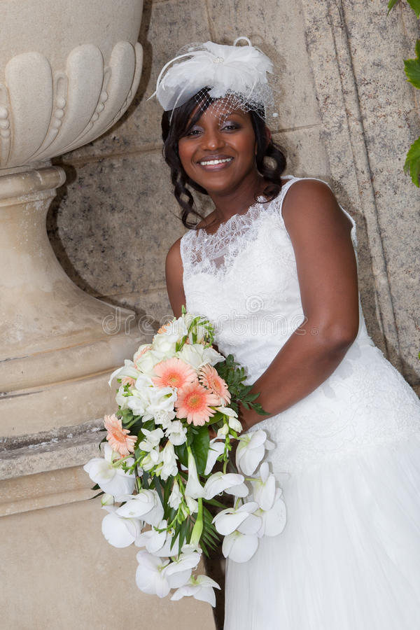 Smiling african beauty bride with bouquet of flower royalty free stock images