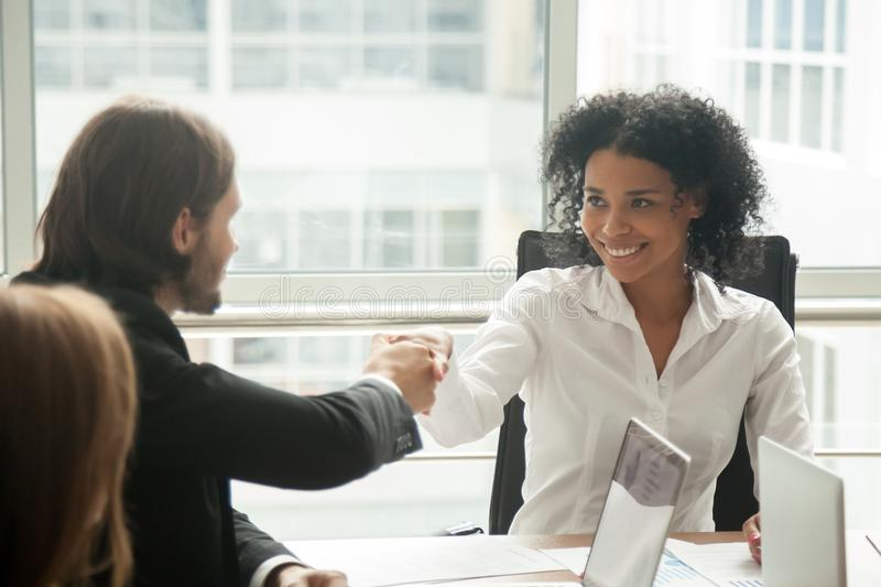 Smiling african businesswoman and caucasian businessman shaking. Hands at meeting, black female boss handshaking welcoming new partner happy to start stock images
