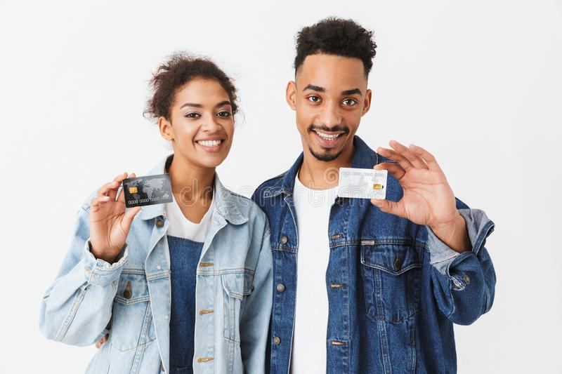 Smiling african couple in denim shirts holding credit cards royalty free stock photo