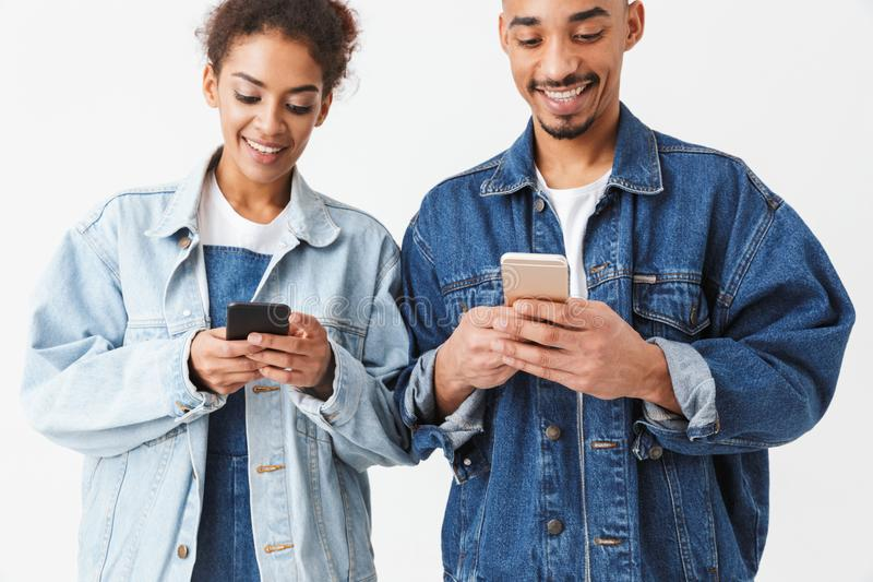 Smiling african couple in denim shirts writing messages on smartphones stock photography