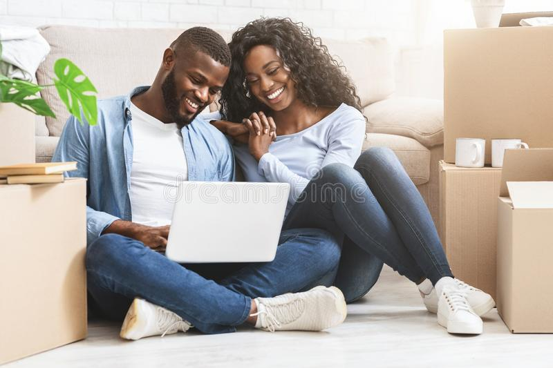 Smiling couple sitting on floor at new apartment, using laptop stock image