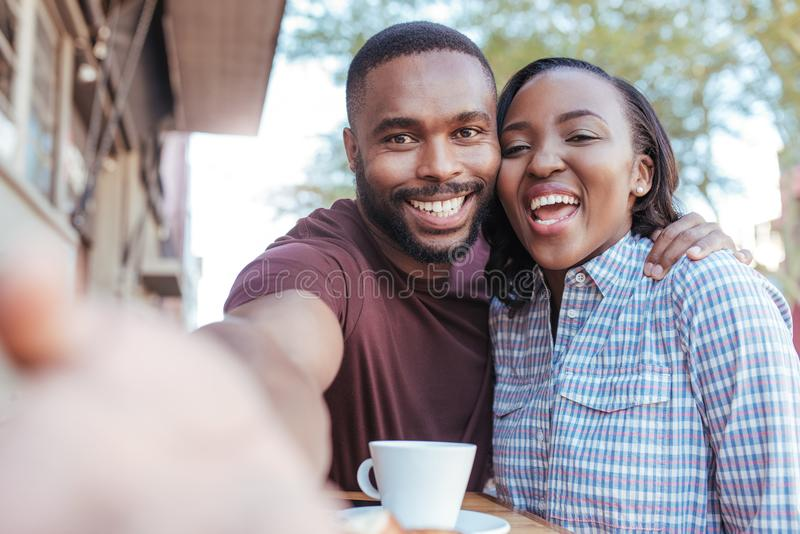 Smiling African couple taking selfies together at a sidewalk cafe royalty free stock photo