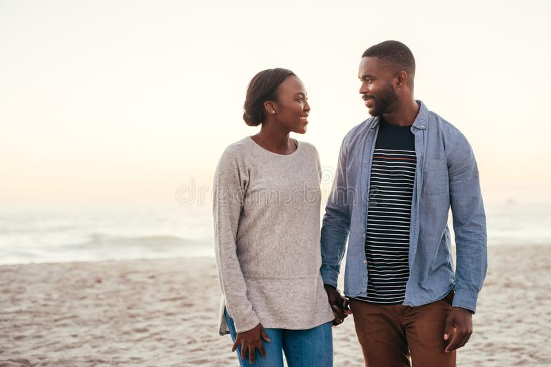 Smiling African couple walking together along a beach at sunset stock images