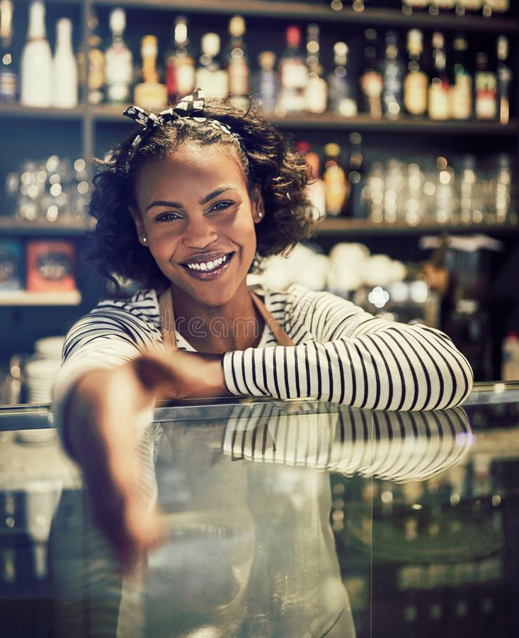 Smiling African entrepreneur shaking hands from behind her cafe stock photos