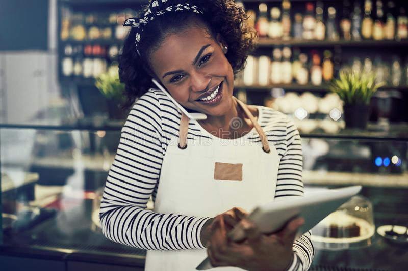 Smiling African entrepreneur talking on the phone in her cafe stock photo