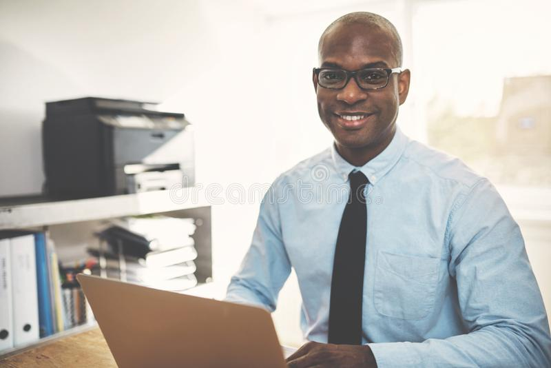 Smiling African entrepreneur working online in a home office royalty free stock photos