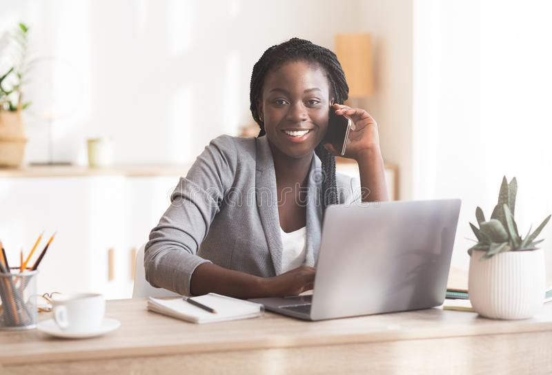Smiling african female manager talking on cellphone consulting client stock images