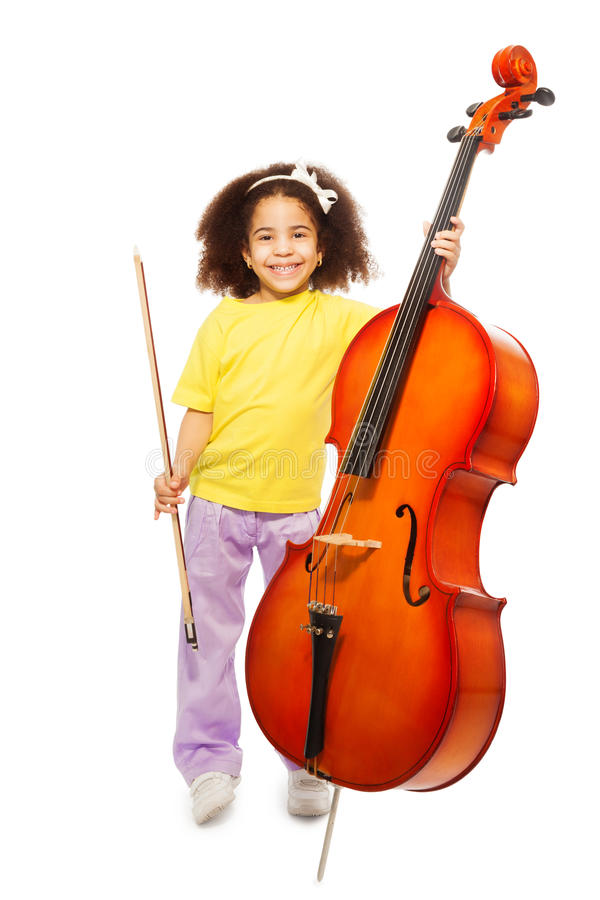 Smiling African girl holding cello and fiddlestick. Smiling African girl holding cello with fiddlestick ready to play standing on the white background stock photos