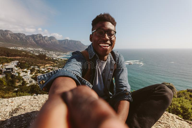 Smiling african guy on top of a mountain taking selfie stock photography