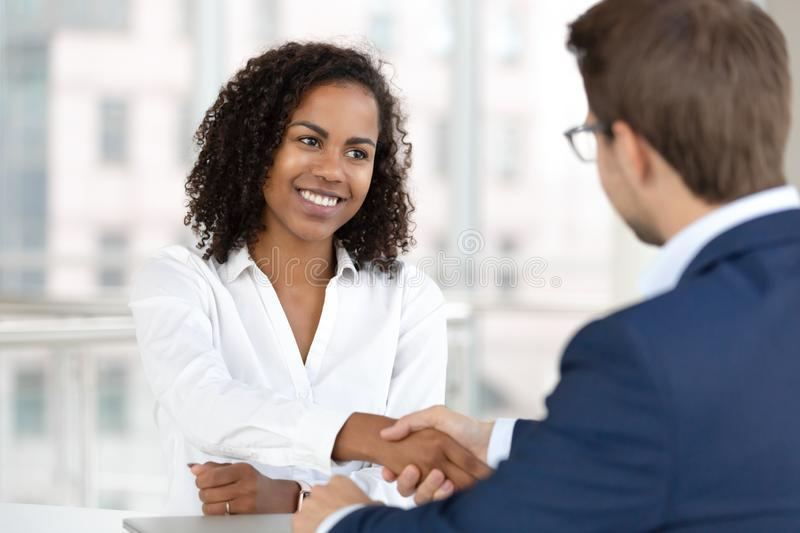 Smiling african hr manager handshake hire candidate at job interview. Smiling african female hr manager handshake hire male candidate at job interview make good royalty free stock photography