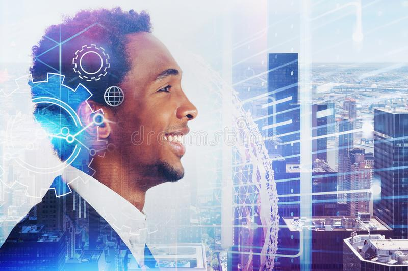 Smiling African man in city, gears and internet. Side view of smiling young African American businessman in city with double exposure of gears and internet stock photo