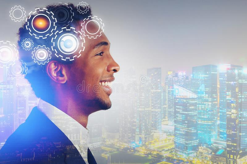 Smiling African man in night city, gears. E view of smiling young African American businessman in night city with double exposure of gears. Concept of stock images
