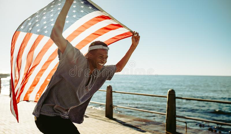 Cheerful young guy at promenade with american flag royalty free stock image