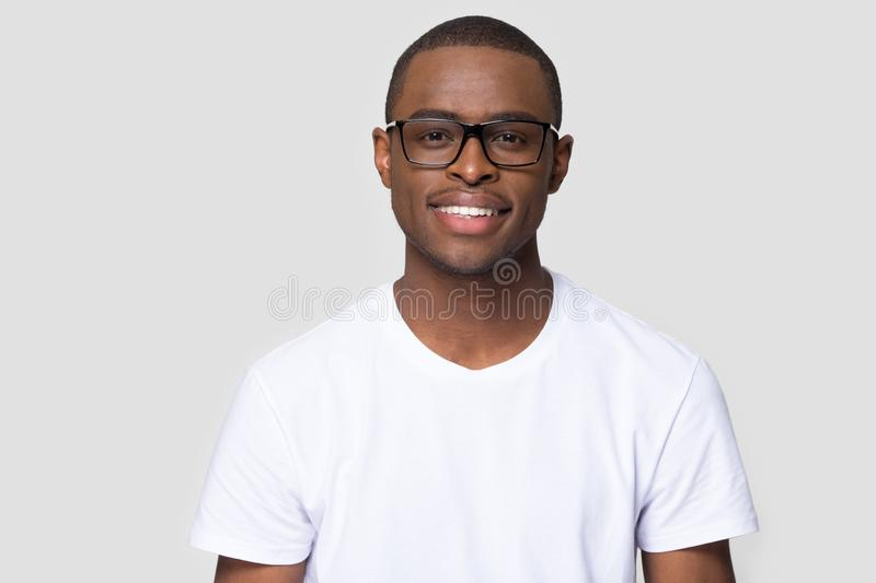 Smiling african millennial man looking at camera isolated on background stock photos