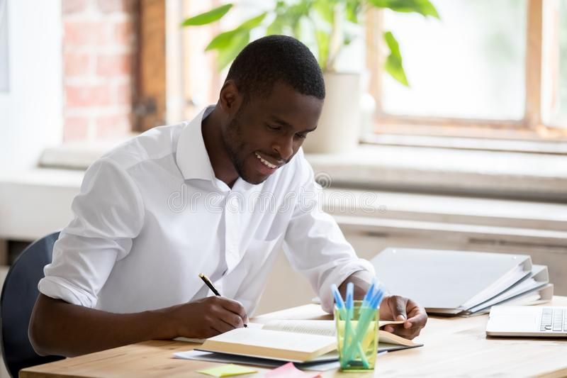 Smiling african student holding pen making notes preparing for test royalty free stock photo