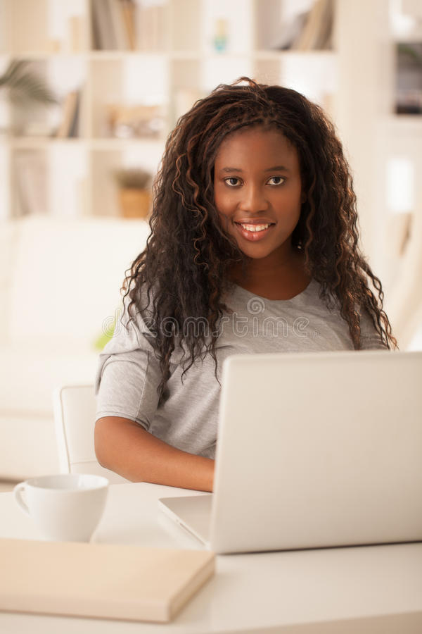 Smiling African Teenage Girl Using Laptop at Home royalty free stock image