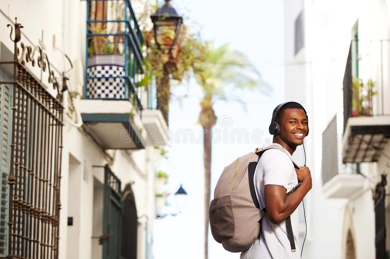 Smiling african travel man with bag listening to music. On headphones stock photo