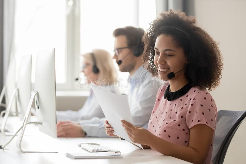 Smiling african woman call center operator wearing headset reading papers. Smiling african american businesswoman call center operator agent wearing headset stock photo
