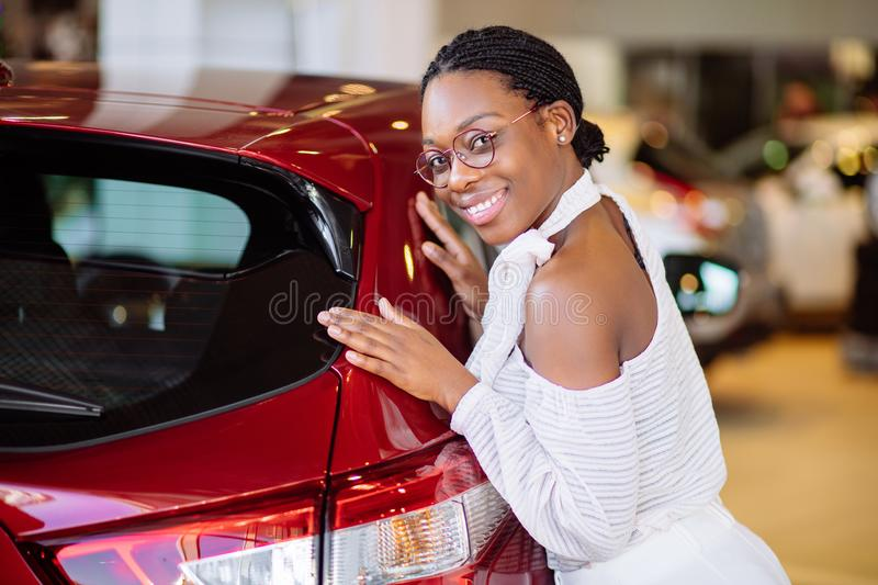 Smiling african woman hugging red car at new car showroom royalty free stock photo