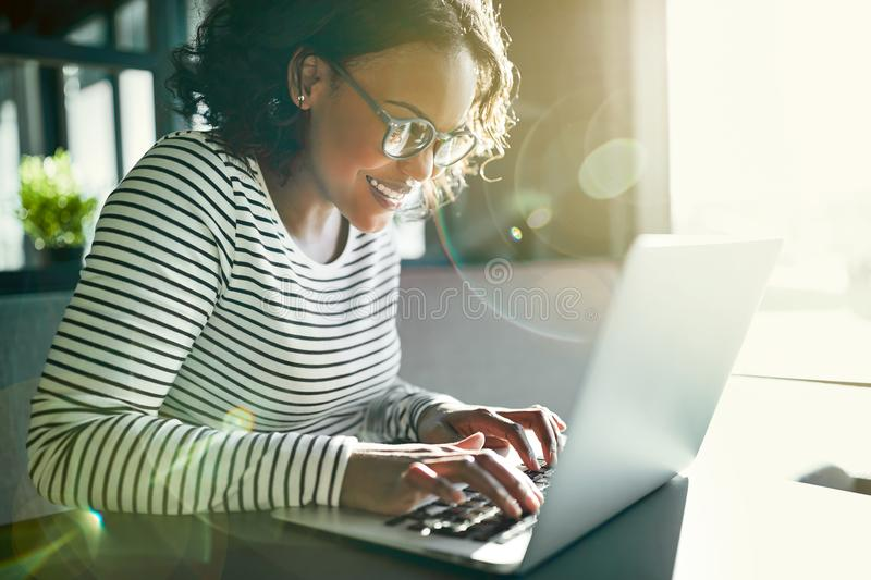 Smiling African woman sitting at a table working online stock image