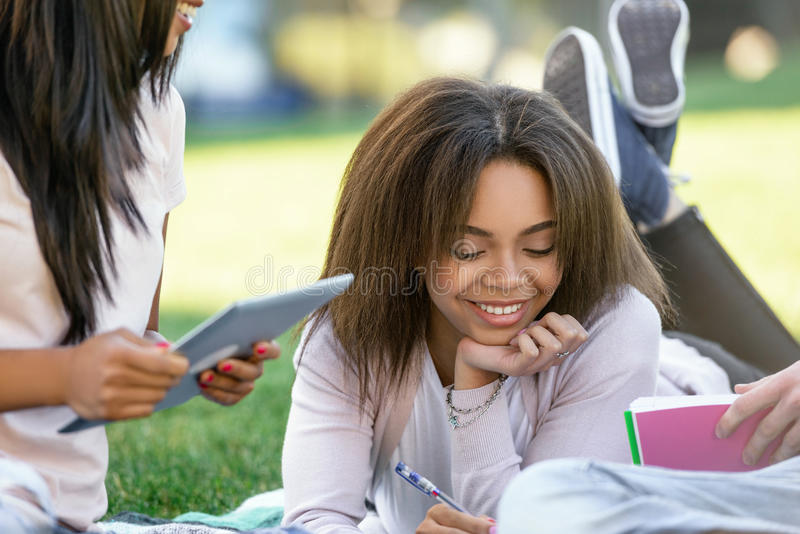 Smiling african woman student studying outdoors. Looking aside. royalty free stock images