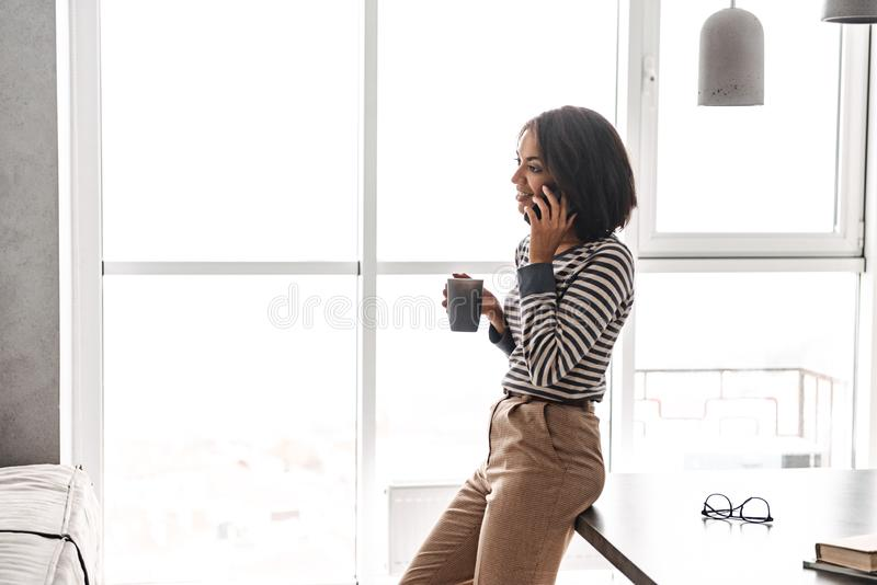 Smiling african woman using mobile phone. While standing at the kitchen and drinking coffee stock images