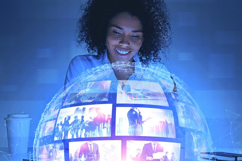 Smiling African woman watching streaming video. Smiling young African American women looking at futuristic video streaming interface. Concept of hi tech and stock photography
